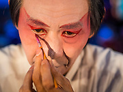 "30 JUNE 2016 - BANGKOK, THAILAND: Performers put on their makeup before a Chinese opera performance at Chiao Eng Piao Shrine in Bangkok. Chinese opera was once very popular in Thailand, where it is called ""Ngiew."" It is usually performed in the Teochew language. Millions of Chinese emigrated to Thailand (then Siam) in the 18th and 19th centuries and brought their culture with them. Recently the popularity of ngiew has faded as people turn to performances of opera on DVD or movies. There are about 30 Chinese opera troupes left in Bangkok and its environs. They are especially busy during Chinese New Year and Chinese holidays when they travel from Chinese temple to Chinese temple performing on stages they put up in streets near the temple, sometimes sleeping on hammocks they sling under their stage.        PHOTO BY JACK KURTZ"