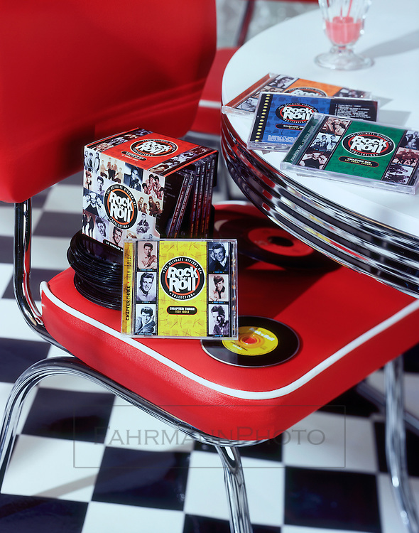 A set of CD's sit atop a chair in a 1950's diner vignette