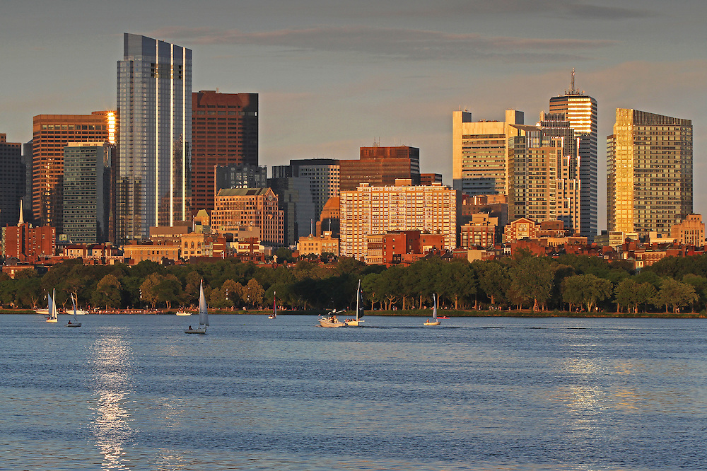 Boston skyline sunset photography featuring iconic skyscrapers and the third tallest in the city: The Millennium Tower. The foreground is made off building reflections in the Charles River and sailboats cruising along. The Millennium Tower, with its nickname Millie, is located at Downtown Crossing and is one of the latest Boston urban architecture skyline addition. Boston skyline photos are available as museum quality photography prints, canvas prints, acrylic prints or metal prints. Fine art prints may be framed and matted to the individual liking and decorating needs:<br />