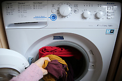 A person takes the laundry out of a washing machine in a London home. Picture date: Wednesday April 1, 2020.