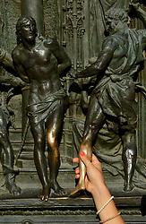 THEMENBILD - Die Lombardei ist eine norditalienische Region mit einer Fläche von 23.863 km und ca.9,8 Mio. Einwohnern. Sie ist in zwölf Provinzen aufgeteilt und liegt zwischen Lago Maggiore, Po und Gardasee. Bilder aufgenommen am 21. August 2013, im Bild Wuensche, Frau beruehrt Bein Detail bronzenes Portal mit Szenen aus dem Leben Marias, Kirchenmotive, Bildhauer Lodovico Pogliaghi, Westfassade Kathedrale Mailaender Dom oder Duomo di Santa Maria Nascente, // THEMES PICTURE - Lombardy is a northern Italian region with an area of 23,863 km and a population of 9,8 Mio. It is divided twelve provinces and is situated between Lake Maggiore, Lake Garda and Po. Pictured on 2013/08/21. EXPA Pictures © 2013, PhotoCredit: EXPA/ Eibner/ Michael Weber<br /> <br /> ***** ATTENTION - OUT OF GER *****