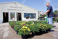 Douglas Slaymaker, of Marion, waters the mums out front at Frontier Garden Center, 1941 Blairs Ferry Road NE, in Cedar Rapids, on Thursday, September 8, 2011.