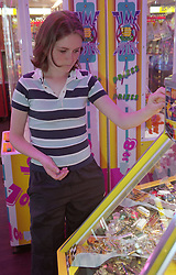 Young homeless girl putting coin into slot machine in seaside arcade,