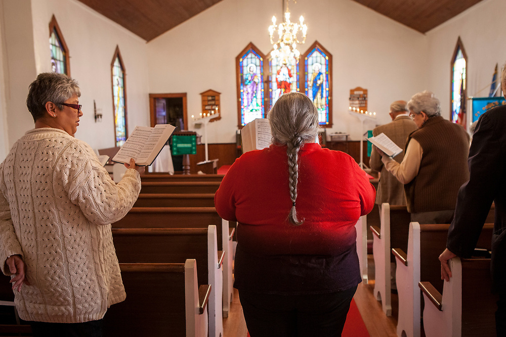 Monacan Chief, Sharon Bryant, center, performs the Sunday service inside the St. Paul's Episcopal Church, in Amherst, VA.  Bryant was in the process of becoming an ordained minister before she died of cancer in July, 2015.  The mission church was founded in 1908 and further strengthened the bond of those families that stayed in the Bear Mountain settlement by creating a school for children to attend.   The church, tribal hall and ancestral museum are all adjacent to each other, forming the center of the Monacan community in Amherst, VA.