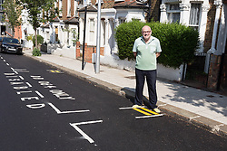 "© Licensed to London News Pictures. 09/07/2015. London, UK. Local resident, Steven Taylor stands by newly painted minature double yellow lines in Mossbury Road, Clapham Junction. The new tiny double yellow lines, measure approximately one foot in length and appeared after Wandsworth Council resurfaced and painted the road. There are two identical sets either side of a disabled parking bay. Owner of one of the properties behind the new road markings, Steven Taylor (not pictured) says ""They're so funny, what on earth could you park in there? They're not even big enough for a bike."" Photo credit : Vickie Flores/LNP"