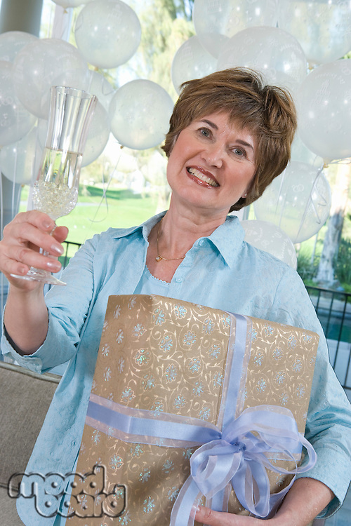 Woman holding gift and glass of champagne at party
