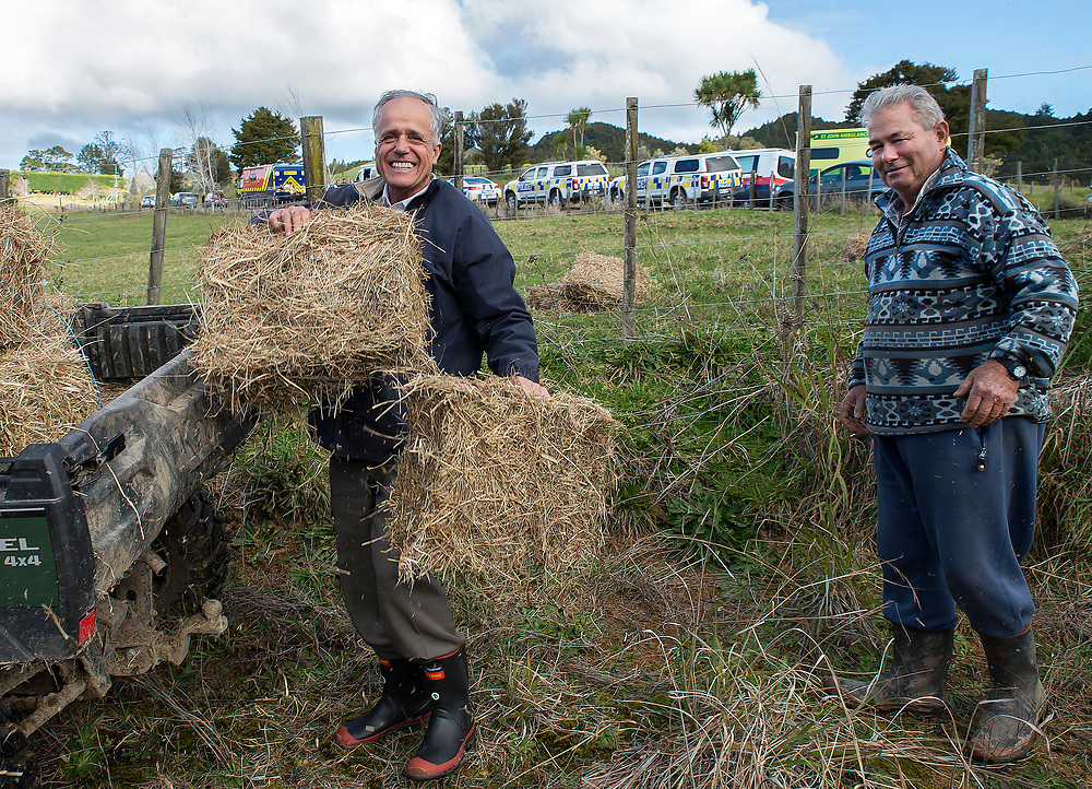 Two farmers move hay as there farm road was blocked by a armed police cordon on Mt Tiger Road after two women were found dead and a man was taken to hospital with gunshot wounds, with the house at the centre of attention now having been engulfed in fire, Whangarei, New Zealand, Wednesday, July 26, 2017. Credit:SMPA / Malcolm Pullman   **NO ARCHIVING**