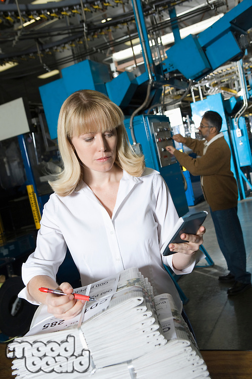Woman using calculator and checking newspaper in factory