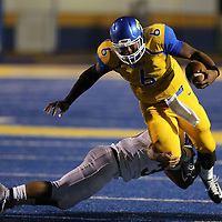 Tupelo quarterback Stephon McGlaun jumps over a Columbus defender looking to gain more yards in the first quarter.