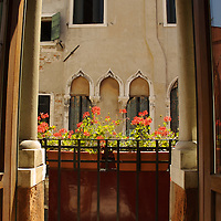 Italian building with small balcony with flowers in Venice