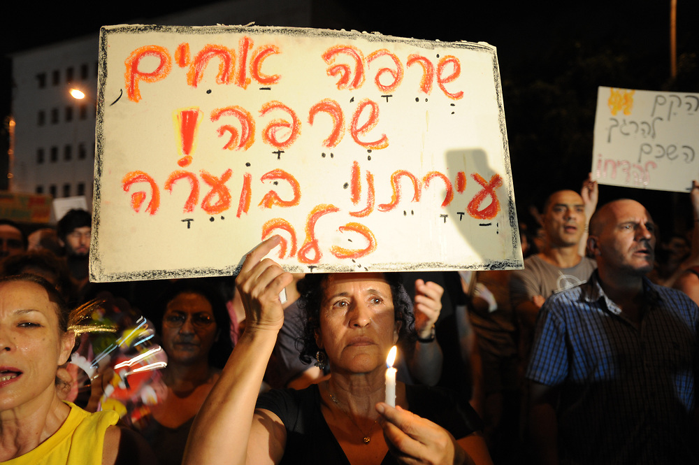 An Israeli woman hods a placard and acandle protests during a demonstration in Tel Aviv on July 21, 2012, in memory of Moshe Silman, an Israeli protester who set himself alight during a social justice demonstration on July 14. Silman struggled for his life after suffering from extensive burns and died at Tel Hashomer hospital near Tel Aviv, on July 20. Photo by Gii Yaari