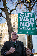 With his back to the Ministry of Defence main building in Whitehall, an elderly gentleman protests about war not welfare in Whitehall before Saudi Crown Prince's Mohammed bin Salman's meeting with Prime Minister Theresa May in Downing Street, on 7th March 2018, in London England.
