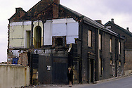 Man walking past boarded up buildings on the site of the demolished Brown Bayley steel works....