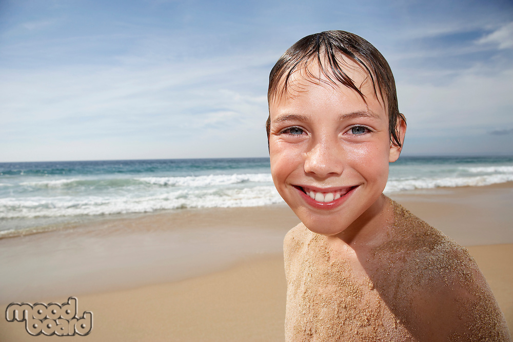 Boy (10-12) covered in sand smiling on beach portrait