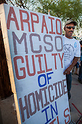 "23 JUNE 2012 - PHOENIX, AZ:  A human rights activist pickets the Maricopa County Jail in Phoenix Saturday afternoon. About 2,000 members of the Unitarian Universalist Church, in Phoenix for their national convention, picketed the entrances to the Maricopa County Jail and ""Tent City"" Saturday night. They were opposed to the treatment of prisoners in the jail, many of whom are not convicted and are awaiting trial, and Maricopa County Sheriff Joe Arpaio's stand on illegal immigration. The protesters carried candles and sang hymns.      PHOTO BY JACK KURTZ"