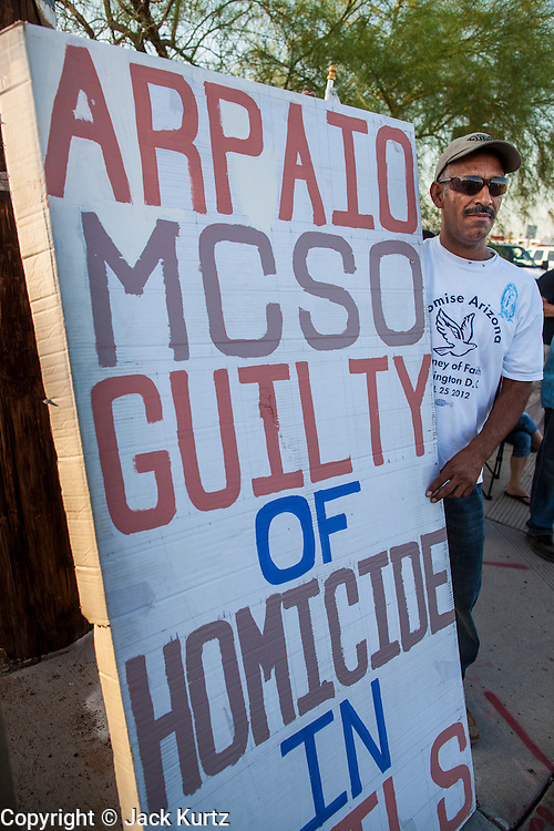 """23 JUNE 2012 - PHOENIX, AZ:  A human rights activist pickets the Maricopa County Jail in Phoenix Saturday afternoon. About 2,000 members of the Unitarian Universalist Church, in Phoenix for their national convention, picketed the entrances to the Maricopa County Jail and """"Tent City"""" Saturday night. They were opposed to the treatment of prisoners in the jail, many of whom are not convicted and are awaiting trial, and Maricopa County Sheriff Joe Arpaio's stand on illegal immigration. The protesters carried candles and sang hymns.      PHOTO BY JACK KURTZ"""