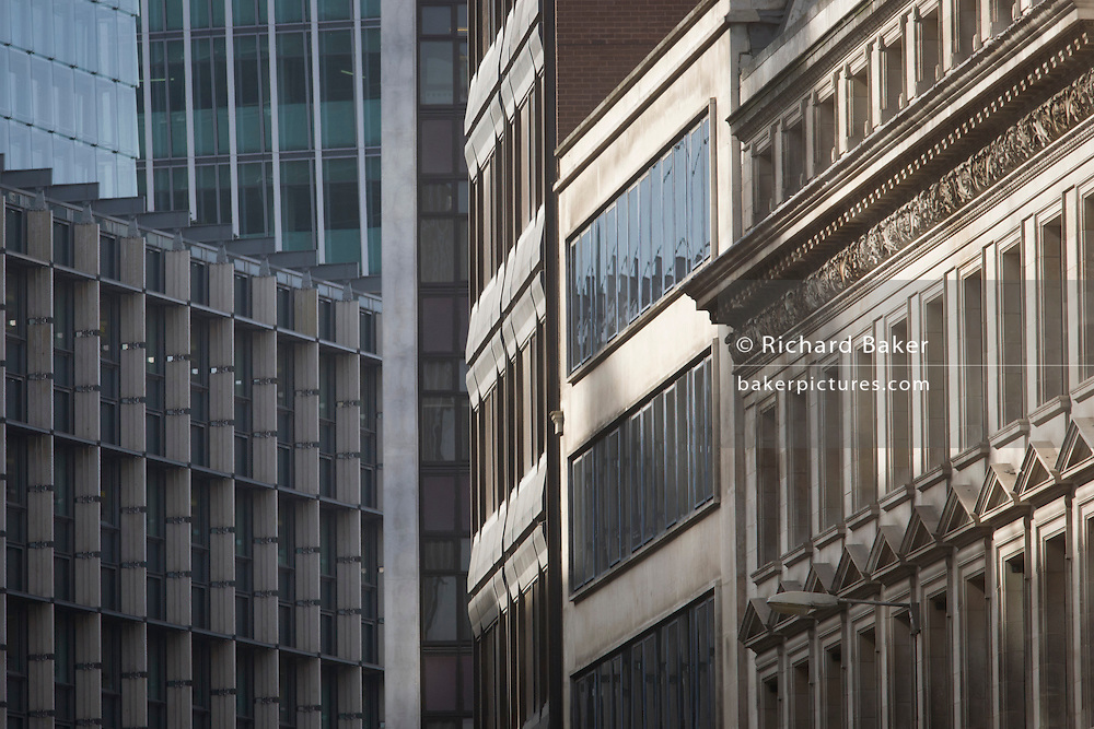 Mixed architecture of generic City of London office buildings in Fenchurch Street in the heart of the capital's financial district. We see at a distance from along this busy city road, the headquarters of banking institutions and insurance companies whose offices are a mixture of styles and eras. 21st Century architecture is on the left and turn-of-the-20th century to the right. There are no company logos or signs and so remain generic and anonymous.