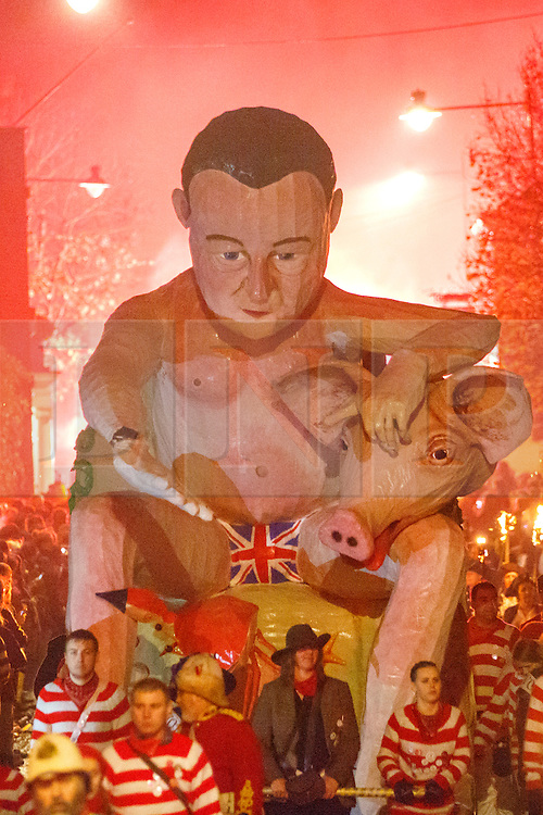 © Licensed to London News Pictures. 05/11/2015. Lewes, UK. A David Cameron effigy is carried during a bonfire parade in Lewes, Sussex during the traditional Bonfire Night celebrations on Thursday, 5 November, 2015. Thousands of people attend the parade through the narrow streets of Lewes and burn effigies to celebrate Guy Fawke night. Photo credit: Tolga Akmen/LNP