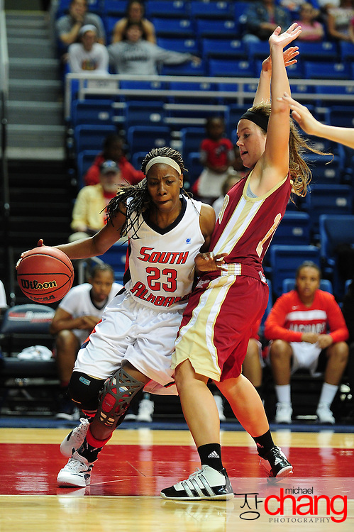South Alabama's guard, Mary Nixon (23), dribbles around a Denver player in the second half of play in Mobile, AL. South Alabama defeated Denver 57-51 on Jan 7, 2012..