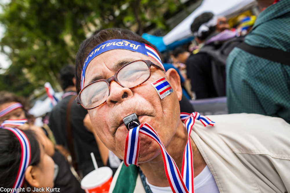 24 NOVEMBER 2013 - BANGKOK, THAILAND: Anti-government protestors blow whistles to make noise during their protest on Rathchdamnoen Ave in Bangkok. More than 400,000 people packed onto Ratchdamnoen Ave in Bangkok Sunday, continuing an anti-government protest that started weeks ago over a blanket amnesty bill passed by the Thai Parliament. The amnesty bill was defeated in the Thai Senate and the protest morphed into a general protest against the government. The protestors are allied with the Thai Democrat party, the opposition party in parliament. Tens of thousands of pro-government Red Shirts have come to Bangkok to defend the government and are rallying in a different part of the city. Police have warned of clashes between the two groups but as of Sunday evening no problems had been reported. The protestors allege that the amnesty would allow fugitive former Prime Minister Thaksin Shinawatra to return to Thailand.        PHOTO BY JACK KURTZ