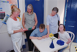 Mothers helping teenage children with Downs Syndrome choose from menu in café,