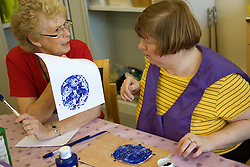 Woman Day Service Officer chatting to a service user with learning disability whilst she paints a clay modeling clay shape,