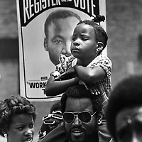 A child sits on her father's shoulders during a civil rights and voting rights march in Alexandria, VA in the early 1980s.
