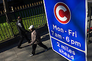 Two pedestrians walk beneath a motorists' Congestion Zone sign on a London street.
