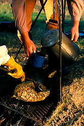 two people preparing breakfast on a campfire