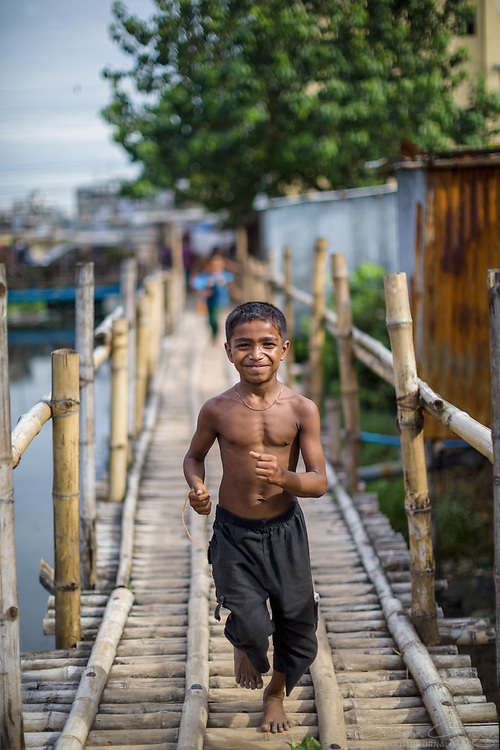 "A boy runs across a bridge at the entrance to a ""slum"" district"