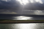 Nederland, Zuid-Holland, Voorne-Putten, 23-10-2013;  zon breekt door de wolken en verlicht de zee. Haringvlietdam met windmolens.<br /> Sun breaks through the clouds and illuminates the sea, Island of South Holland, damn in sea with windmills.<br /> luchtfoto (toeslag op standard tarieven);<br /> aerial photo (additional fee required);<br /> copyright foto/photo Siebe Swart