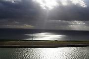 Nederland, Zuid-Holland, Voorne-Putten, 23-10-2013;  zon breekt door de wolken en verlicht de zee. Haringvlietdam met windmolens.<br /> Sun breaks through the clouds and illuminates the sea, Island of South Holland, damn in sea with windmills.<br /> luchtfoto (toeslag op standard tarieven);<br /> aerial photo (additional fee required);<br /> copyright foto/photo Siebe Swart