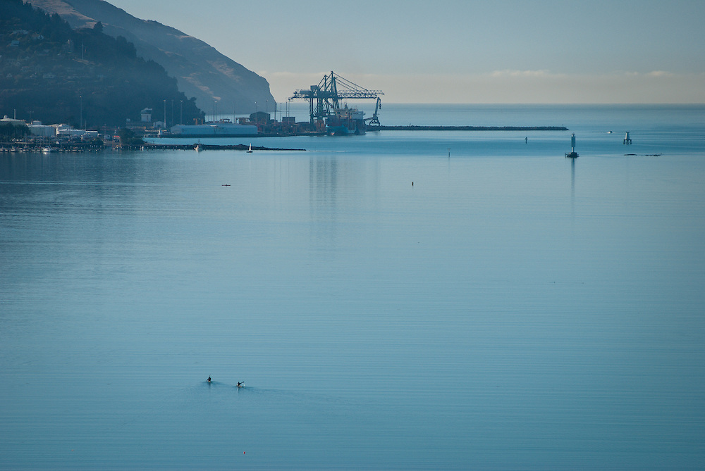 Two canoeists paddle from Governors Bay towards Lyttelton Harbour with cargo terminal in  the distance