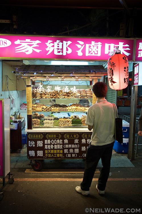 A man shops for local delicacies in Loudong Night Market, Yilan, Taiwan.