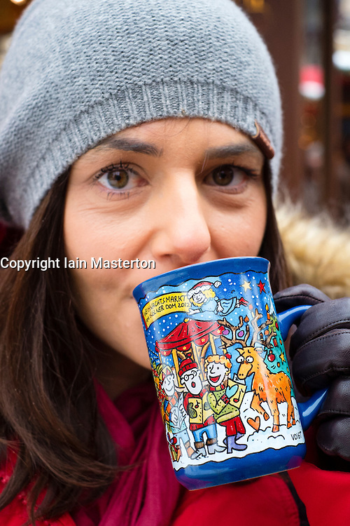Woman drinking traditonal Gluhwein drink at Christmas market in Cologne Germany