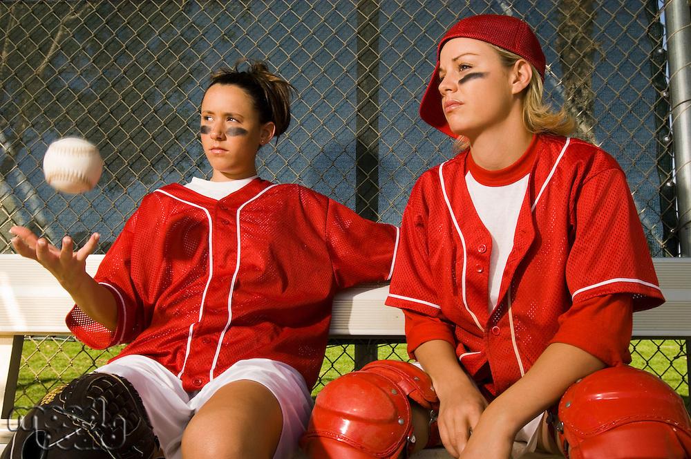 Softball players sitting on bench portrait