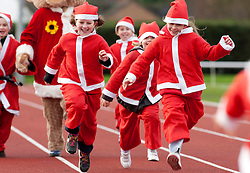 © Licensed to London News Pictures. 11/12/2011, Nuneaton, Warwickshire, UK. Over 200 people dressed in Santa outfits ran a mile to raise money for the Mary Evans Hospice appeal earl;ier today. The charity raised over four thousand pounds last year and organiser Janet Kavangah from the hospice said they were hoping to better that this year. Pictured, fun and laughter as santas race down the home straight. Photo credit : Dave Warren/LNP