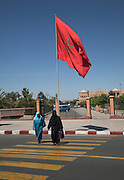 Large red Moroccan flag flying as two Muslim women cross road Marrakech, Morocco, north Africa