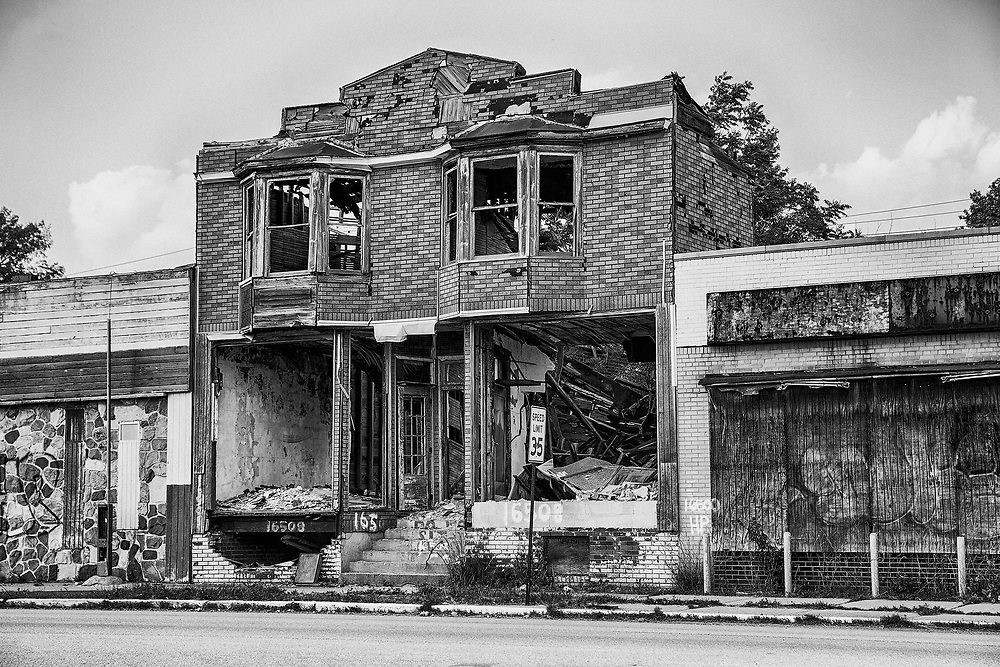 DETROIT, USA - JUNE 9, 2015: A burned out and semi-demolished building between two closed storefronts on Hamilton Avenue in Detroit, Michigan is symbolic of the urban blight that is emblematic of the city.