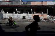 Padang, Western Sumatra, Indonesia, 7th October 2009:?A man runs past collapsed buildings on Jalam Pondok in Padang following a devastating earthquake in Western Sumatra that claimed the lives of an estimated 2000 people.?Photo: Joseph Feil