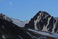 Gibbous moon hangs over mountains of Smeerenburgfjorden along coast of Spitsbergen island; Svalbard, Norway.