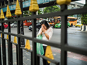 03 SEPTEMBER 2015 - BANGKOK, THAILAND: A woman outside the fence at Erawan Shrine prays as she goes past the shrine. Repairs to Erawan Shrine were completed Thursday, Sept 3 after the shrine was bombed on August 17. Twenty people were killed in the bombing and more than 100 injured. The statue of the Four Faced Brahma in the shrine was damaged by shrapnel and a building at the shrine was damaged by debris.    PHOTO BY JACK KURTZ