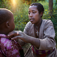 "Wubalem and her daughter Rekebki in the village of Mecha...Wubalem Shiferaw, age 23, lives in the village of Mecha with her husband Tsega Bekele, age 33, and their daughter Rekebki, age 4. Wubalem remembers her grandparents harvesting honey. She has maintained this tradition while moving to modern hives which produce a far greater yield of honey. Wubalem is a member of the Mecha village Cooperative which brings together local women beekeepers allowing them to share insights and build a credit union. The Mecha village Cooperative is not yet a member of the Zembaba Union. Wubalem's husband Tsega is a priest and a tailor. ..Harvesting honey supplements the income of small farmers in the Ethiopian region of Amhara where there is a long tradition of honey production. However, without the resources to properly invest in production and the continued use of of traditional, low-yielding hives, farmers have not been able to reap proper reward for their labour. ..The formation of the Zembaba Bee Products Development and Marketing Cooperative Union is an attempt to realize the potential of honey production in Amhara and ensure that the benefits reach small producers. ..By providing modern, high-yield hives, protective equipment and training to beekeepers, the Cooperative Union helps increase production and secure a steady supply of honey for which there is growing demand both in and beyond Ethiopia. The collective processing, marketing and distribution of Zembaba's ""Amar"" honey means that profits stay within the cooperative network of 3,500 beekeepers rather than being passed onto brokers and agents. The Union has signed an agreement with the multinational Ambrosia group to supply honey to the export market. ..Zembaba Bee Products Development and Marketing Cooperative Union also provides credit to individual members and trains carpenters in the production of modern hives. ..Photo: Tom Pietrasik.Mecha, Amhara. Ethiopia.November 17th 2010"