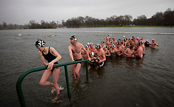 © Licensed to London News Pictures. 25/12/2012. London, UK. Members of the Serpentine Swimming Club exit the river in the pouring rain after they competed in the Serpentine Swimming Club's annual Christmas morning 'Peter Pan Cup' race in Hyde Park, London, today (25/12/12).   The race, which takes place every Christmas Day on the Serpentine River, takes its name from from the novel by J.M.Barrie after the author presented the first Peter Pan Cup in 1904. Photo credit: Matt Cetti-Roberts/LNP