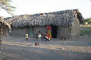Africa, Tanzania, Lake Eyasi National Park Hadzabe family in front of their mud hut April 2007