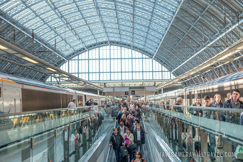 Passengers arrive from Europe on a platform under the distinctive iron and glass arched cover over the platforms of St Pancras Railway Station (now known as St Pancras International). The renovated station features distinctive Victorian architecture and serves as a Eurostar terminal for high-speed trains to Europe. There are also platforms for domestic train services. The distinctive train shed roof was designed by William Henry Barlow.