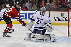 Feb 9; Newark, NJ, USA; Tampa Bay Lightning goalie Dwayne Roloson (30) makes a save while New Jersey Devils center Travis Zajac (19) looks for the rebound during the first period at the Prudential Center.