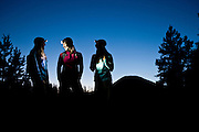 Three women talk during an evening hike by headlamp in Utah's Uinta Mountains.