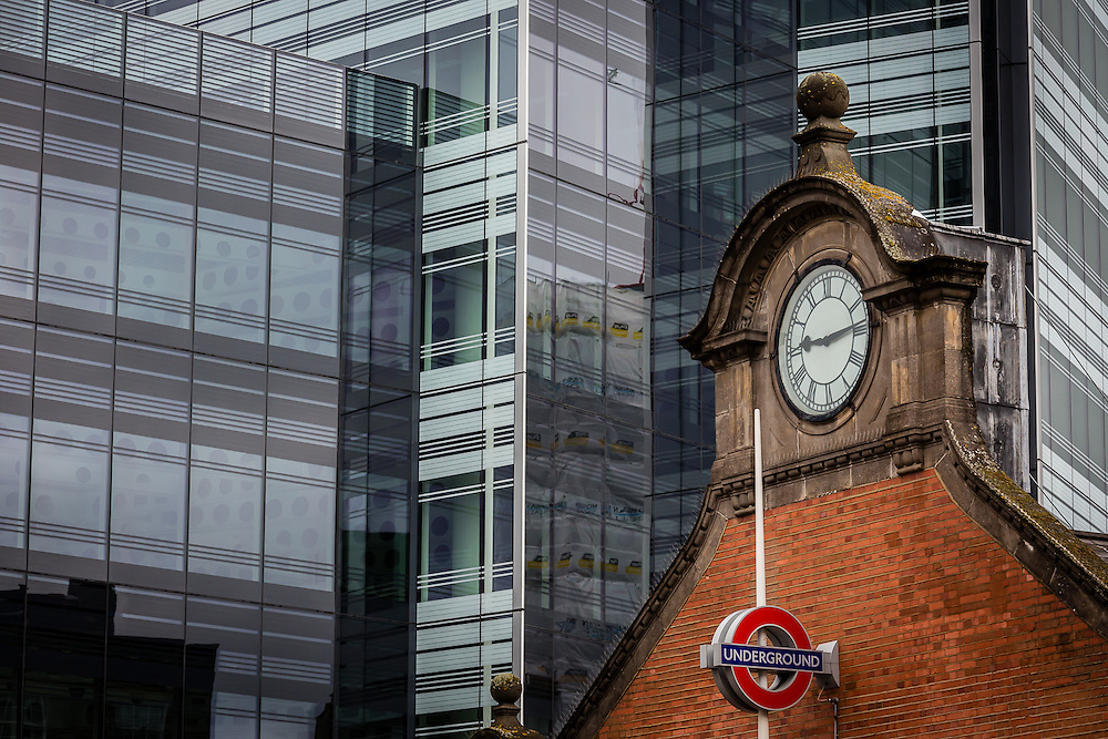 The red brick façade of the old Hammersmith Tube Station clock tower contrasts nicely with the huge glass office building