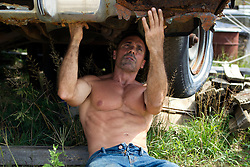 man without a shirt working under a rusted old car